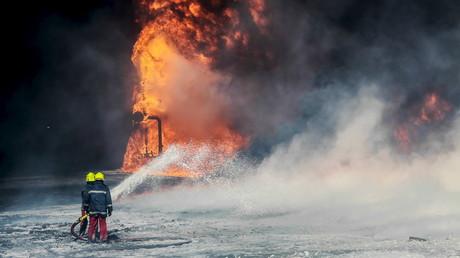 Les pompiers travaillent à éteindre l'incendie sur un des containers de pétrole à Ras Lanouf, en Libye