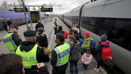 Des policiers rassemblent des réfugiés dans une garde de train de la commune de Malmo