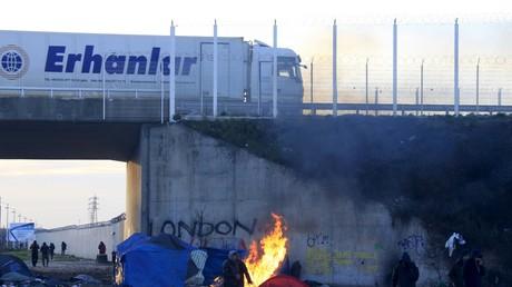 Les migrants se réchauffent les mains à côté d'un feu de bois près du camp de la «Jungle», à Calais, dans le Nord de la France