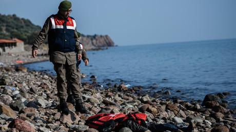 Un garde côte turque regarde le corps d'un enfant recouvert d'un gilet de sauvetage le 30 janvier 2016