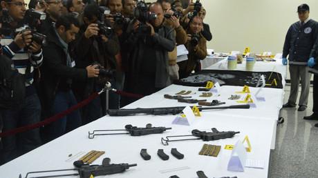Un membre du BCIJ montre les armes saisies aux groupes terroristes au cours d'une conférence de presse le 19 février