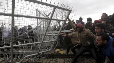 Des migrants tentent de faire tomber une partie de la barrière lors d'une manifestation à la frontière gréco-macédonienne le 29 février 2016