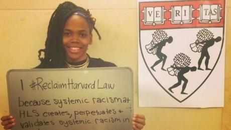 Une élève tient une pancarte contre l'emblème de l'université