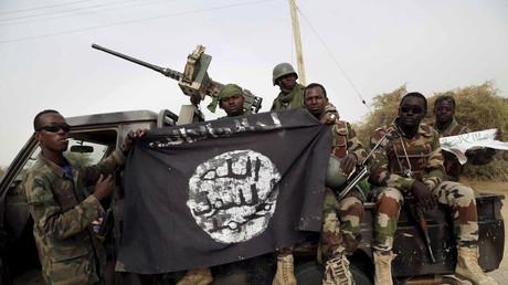 Les soldats nigériens tiennent un drapeau de Boko Haram qu'ils avaient saisi dans la ville de Damasak, au Nigeria