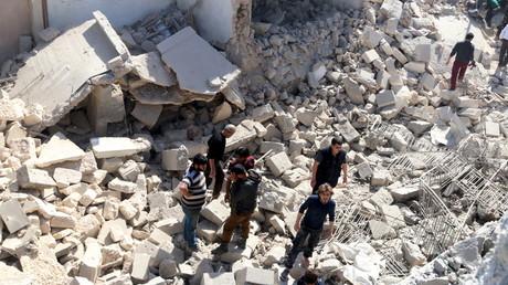 Des civils sur les ruines d'un bâtiment détruit par les bombardements aériens à Alep, le 16 avril 2016