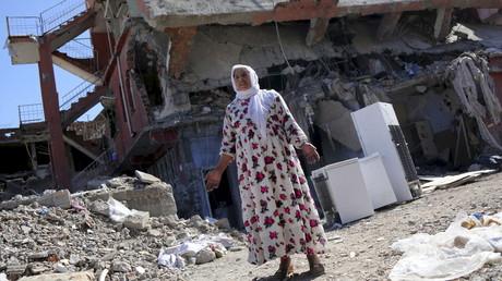 2 Mars 2016 : Une femme devant un bâtiment endommagé lors des affrontements entre les forces de sécurité turques et militants kurdes, dans la ville de Cizre, en Turquie.