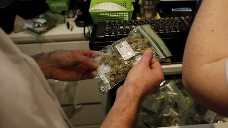 Un client tient un sachet de cannabis médical dans un magasin de Safed, en Israël