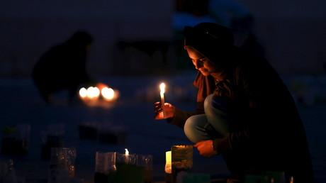 Une jeune femme allume une bougie en soutien de l'armée libyenne