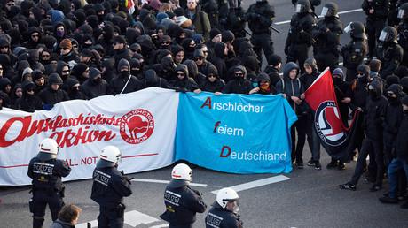 Des manifestants tiennent une bannière parodique Arschloecher feiern Deutschland (qui peut se traduire par