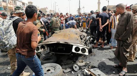 Des habitants de Bagdad sur les lieux d'un attentat à la voiture piégée dans un quartier chiite de la ville, le 11 mai 2016