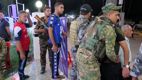 Des membres des forces irakiennes de sécurité procèdent à des fouilles lors d'une cérémonie au café Al-Furat à Balad