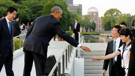 Le président des Etats-Unis Barack Obama, accompagné du Premier ministre japonnais Shinzo Abe (gauche) , salue une écolière au Mémorial de la Paix d'Hiroshima, le 27 mai 2016.