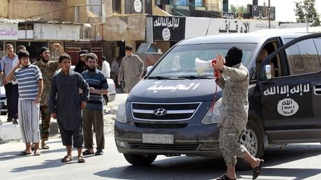 Un combattant de Daesh et des Syriens
