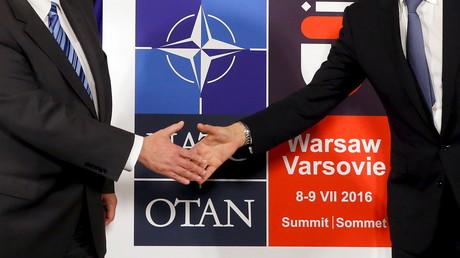 Le ministre des Affaires étrangères polonais et le secrétaire général de l'Otan se serrent la main