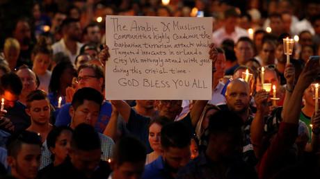 Un homme tient une pancarte sur laquelle est écrit que la communauté musulmane condamne la fusillade qui a eu lieu dans une discothèque gay d'Orlando, le 13 juin à Orlando.