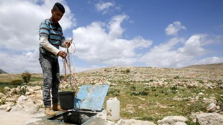 Un palestinien puise de l'eau près de Naplouse