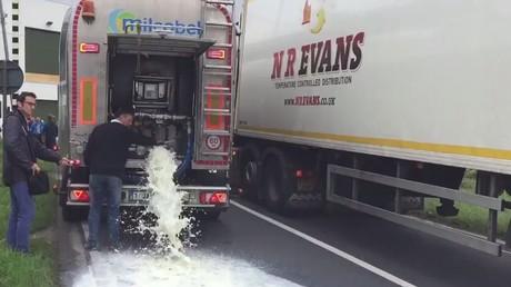 Un producteur de lait déverse sa marchandise à l'entrée de l'usine