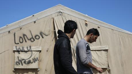 Des migrants dans le camp de Calais qui marchent devant une tente sur laquelle est inscrit «Londres mon rêve», le 24 juin 2016