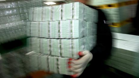 Un homme transporte des piles de billets