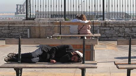 Un sans domicile fixe dort sur un banc près du port d'Alger