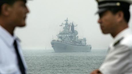 Des officiers de la Marine chinoise attendent à quai alors qu'un navire de guerre chinois escorte l'arrivée de Curtis Wilbur, un destroyer lance-missiles américain, entrant au port de Qingdao, à l'est de la province du Shandong en Chine