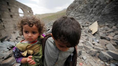 11 août 2016 : un garçon porte sa sœur en marchant sur les décombres d'une maison détruite par une frappe aérienne saoudienne dans la capitale du Yémen Sanaa