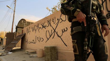 Un soldat des forces spéciales irakiennes devant un mur à Mossoul sur lequel est écrit : «L'Etat islamique restera», le 27 octobre.