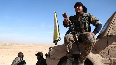 Un combattant des Forces démocratiques syriennes patiente armé sur un véhicule camouflé à l'aide de boue.