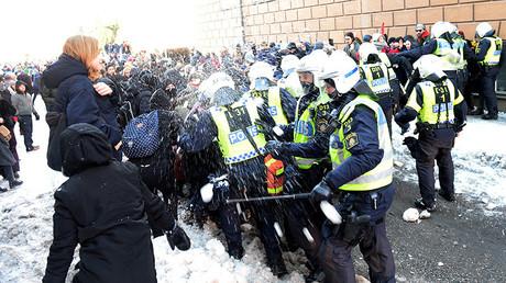 Des contre-manifestants attaquent avec des boules de neige les forces de police les empêchant d'atteindre le lieu de rassemblement des néo-nazis.