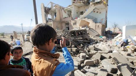 Un enfant prend en photo une maison de Sanaa détruite par un raid aérien de la coalition arabe au Yémen