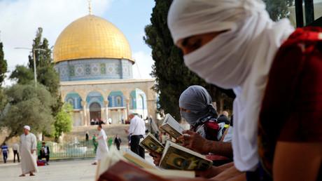 Des palestiniens masqués lisent le Coran près du Dôme du rocher, un lieu saint de l'Islam à Jerusalem