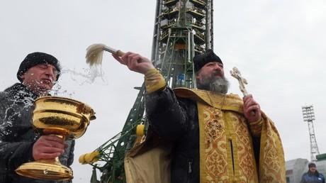 La fusée bénie par un prêtre de l'église orthodoxe