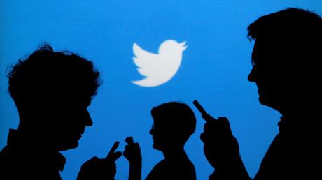 Des silhouettes d'utilisateurs de smartphones devant le logo de Twitter