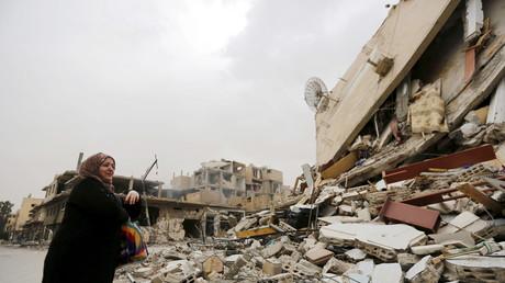 Une femme près de sa maison détruite par les bombardements djihadistes à Palmyre