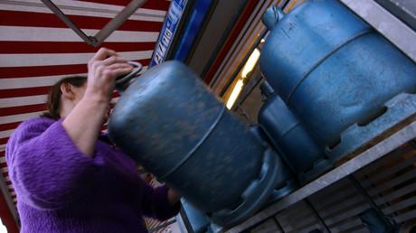 Une femme saisit une bouteille de gaz dans un dépôt