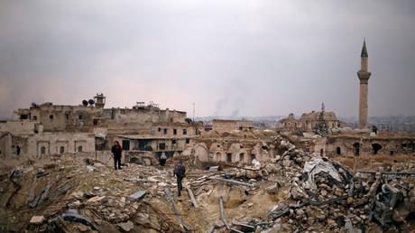 Un soldat de l'armée syrienne avec des civils dans les ruines de l'ancien hôtel Carlton d'Alep.