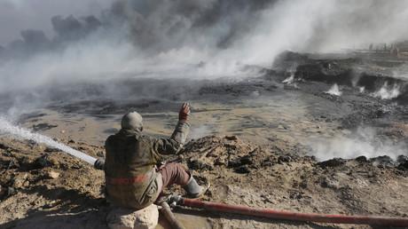 Un employé d'un site pétrolier essaie d'éteindre l'incendie lancé par des combattants de Daesh d'un champs pétrolier à Qayyara, au sud de Mossoul.