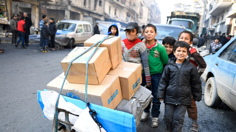 Des enfants poussent un chariot d'aide humanitaire dans les rues d'Alep-est.