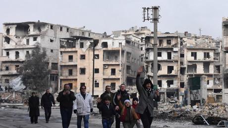 Des civils marchent dans les rues d'un quartier d'Alep est après sa reprise par les forces gouvernementales.