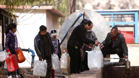 Des gens font la queue pour récupérer de l'eau le 10 janvier dans le quartier d'al-Rabwah dans la banlieue de Damas, sous le contrôle des forces gouvernementales