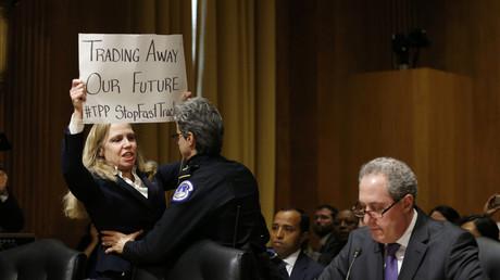 Une militante anti-traité transpacifique se fait évacuer du sénat américain avant l'audition devant les élus du projet d'accord en janvier 2015.