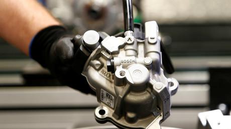 Un employé de Bosch installe un injecteur dans un moteur diesel