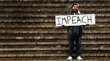 Un homme protestant contre la pésidence de Donald Trump sur les marches de Federal Hall à New York