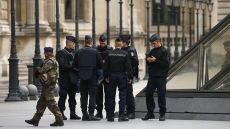 Un militaire et les gendarmes devant le pyramide du Louvre