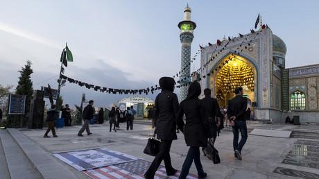Des gens marchent sur les drapeaux israélien et américain à Téhéran