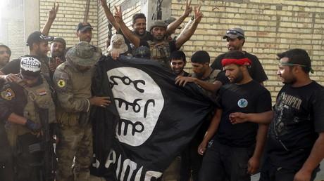 Des militaires irakiens avec un drapeau de Daesh dans la ville de Ramadi libérée de terroristes, juillet 2015