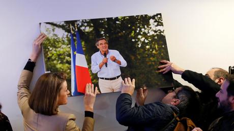 Les journalistes accrochent au mur la photo de François Fillon qui est tombée lors de la conférence de presse.