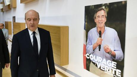 Alain Juppé passe devant une affiche de campagne de François Fillon pour assister au meeting de ce dernier à Bordeaux en février 2017.