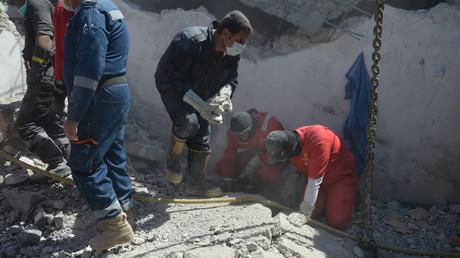 Des pompiers cherchent des corps dans les décombres après une frappe aérienne à Mossoul le 27 mars