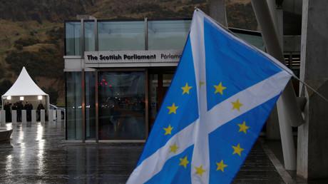 Un drapeau écossais portant les étoiles de l'Union européenne flotte devant le parlement régional écossais